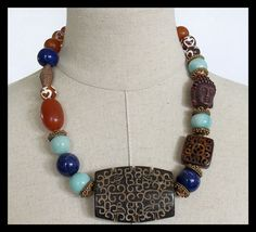 1 of a Kind! Dramatic hand carved Jade focal takes centerstage and is surrounded by large Lapis and Amazonite beads with vintage, handmade copper and brass bead caps. Etched Tibetan Carnelian, handmade amber resin, hand carved antiqued bone square and hand carved stone Goddess (Quan Yin) complete this one of a kind statement necklace. Fastens with my signature, large, fancy handforged bronze claps and soldered link brass chain. Adj from about 20 - 22 inches.