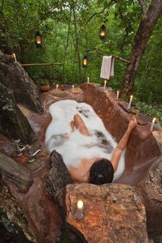 i am not sure how this fits into home, a woman taking a bath in the woods with rocks, alrighty then