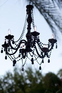 Create a dramatic black chandelier by painting a brass light fixture and adding beads and prisms.