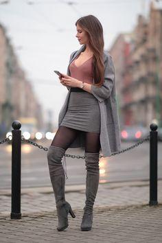 Szary płaszcz, pastelowy sweter, szara spódniczka mini i zamszowe kozaki za kolano