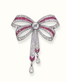 A BELLE EPOQUE RUBY AND DIAMOND BROOCH   Designed as a calibré-cut ruby, old mine and old European-cut diamond ribbon bow, gathered by a collet diamond, to the ruby terminals and pear-shaped diamond drops, circa 1910  Numbered 39275