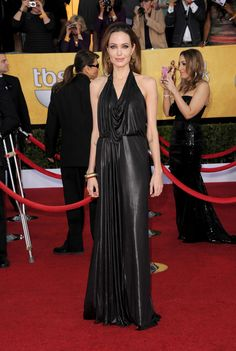 Va-Va-Voom! See the Sexiest Dresses to Hit the Red Carpet in 2012 : Angelina Jolie was smoking hot in a black, liquidy metallic Jenny Packham halter gown at 2012 SAG Awards. To top it off, Angelina wore oversize, gold-and-black vintage-inspired earrings, a gold bangle cuff, and a black envelope clutch.