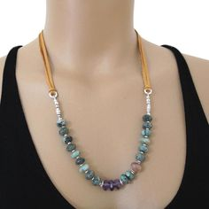 Beautiful organic Emeralds loaded with natural inclusions, three purple Amethysts, an organic Sunstone and handmade fine silver beads are wrapped to soft deer skin. It can be tied to any length up to approx. 32. Wabi-Sabi - the beauty of imperfection All metal is solid .970 fine silver and