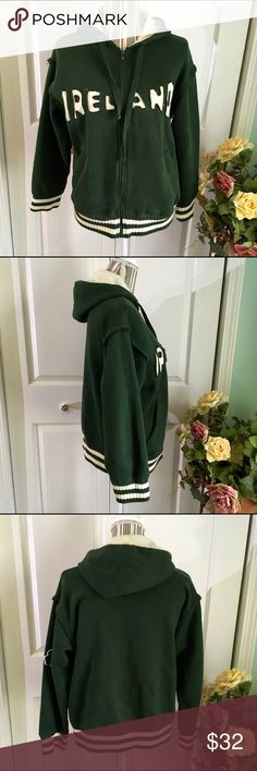 """RETRO CLASSICS Green/Cream Stitched Ireland Hoodie This Retro Classics hooded zip up sweatshirt is in deep green and cream colors with ribbed cuffs and bottom hem. Unique stitching of """"Ireland"""" across the chest with a three leaf clover appliqué on the left sleeve. Warm, soft, and a conversational piece for your wardrobe 😍  Size M, measurements are approximate: - 21 inches underarm to underarm  - 19.5 inches across bottom  - 25 inch sleeves  - 23.5 inches shoulder to hem   Perfect condition…"""