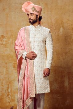 A glamorous attire which can take your celebration to a next level is this white peach coloured wedding sherwani in exclusive raw silk.The sherwani is elevated with stone work all over it,the elegant artistic buttons becomes the center of attraction of this sherwani.The sherwani is concealed with mandarin collar,full sleeves & vented hem.Make your special day more emerging by wearing this wedding sherwani.It comes with matching bottom. Sherwani For Men Wedding, Wedding Groom, Wedding Men, Kurta Pajama Men, Indian Groom Wear, Suit Fashion, Mens Fashion, Groom Dress, Long Jackets