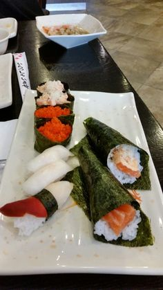 Assorted hand rolls and sushi.