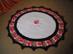 Tapete decorativo circular, com bordas em flores. Técnica: crochê em barbante colorido.