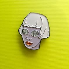 """Spiral Eyes Girl Enamel Pin She's hypnotizing! This girl with spiral eyes and lavender skin is our newest 1.25"""" soft enamel pin and she's perfect for your collar or bag."""