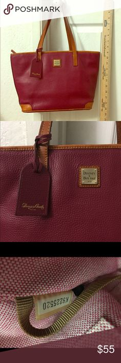 Dooney and Bourke handbag Pre loved purse. Good condition. Normal leather wear on the bottom of the bag. See photo, light stain on the inner bottom lining, pen marks on inner pocket and outer pocket, other wise good condition. Priced based on flaw. From a smoke free home. Dooney & Bourke Bags