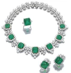 Emerald and diamond necklace, ring and a pair of earrings. The necklace has 7 step cut emeralds framed with diamonds, the cluster spacers set with similar stones mounted in white & yellow gold. Ear clips center on a step cut emerald with diamond borders, mounted in white gold. The ring is flanked with triangular stones, mounted in platinum