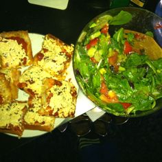 Vegan pizza and salad with cucumber, avocado, tomatoes, basil, fresh lime, olive oil, balsamic vin, pepper, sea salt.