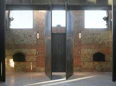 Hangar 16 by Iñaqui Carnicero Architecture.  Pivoting steel doors.