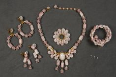 MIRIAM HASKELL FIVE PIECE PARURE: Pink and white beads in various forms, girondole necklace, circle pin, memory wire cuff bracelet and hoop and drop earrings. Signed.