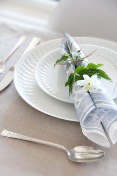 une belle serviette en papier pliée et décorée d'une fleur blanche