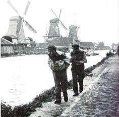 Wat een job - bewri - Een tweetal jagers trekt een vrachtschuit langs het jaagpad van de Rotterdamse Schie. Op de achtergrond de houtzaagmolens Bruinvis, Jacobus en Nieuwe Werklust van de houthandel Van Stolk. De foto dateert uit 1906