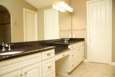 Double vanity sink, ceramic tile, granite countertops, painted cabinets, and polished chrome accessories.