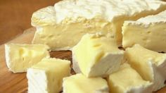 Soft brie cheese cubes on rustic wooden board - HD stock video clip