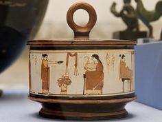A group of women.     Attic white-ground pyxis (cosmetic box) with ring handle. Diameter: 15.24 cm. Height: 15.85 cm Made in Attica. 440-450 BC London, The British Museum