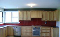 USR supplied and installed this red glass kitchen splashback , the colour highlight the beauty of the natural timber cupboards in this Launceston home.