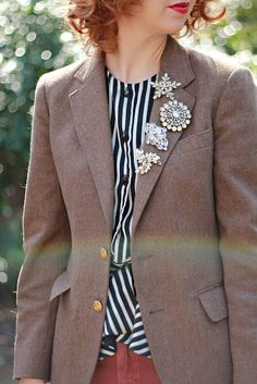 vintage brooches on blazer lapel.