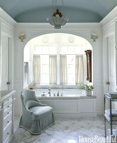 The glossy barrel ceiling in the master bath is painted in Farrow & Ball's Skylight. P. E. Guerin tub fixtures. DeAngelis chair in Empress Satin by Fret Fabrics.   - HouseBeautiful.com
