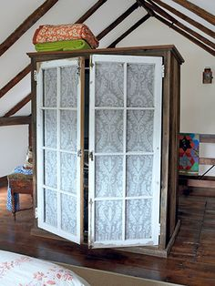 In lieu of a closet, store clothes in a lace-lined armoire made from reclaimed wood and salvaged windows.