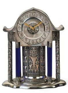 Mantle clock, Moritz Hacker, Vienna, c. 1910, silver plated metal, cobalt blue glass columns, on a moulded oval base, elaborately decorated case, gilded hands, Kienzle movement, eight days running period