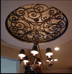 The ornamental ceiling medallion looks like it is made of iron but it is actually custom made from a composite wood material - faux iron. material Faux Wrought Iron Ceiling Medallion Over Chandelier. Ceiling Decor, Ceiling Design, Ceiling Lighting, Foyer Lighting, Ceiling Detail, Accent Lighting, Wall Decor, Home Interior, Interior Design