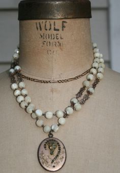 These amazing vintage mother of pearl rosary beads are absolutely breath taking. They are very old and a very lovely old brass locket hangs from it. The locket has old deep red stones with a lady's profile on the front. The necklace is connected by a sterling silver hook and has a beautiful rosary cross that hangs from the back. This is a very stunning piece.