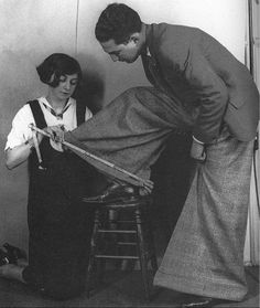 """Oxford bags trousers c. 1920 -- Oxford bags were a loose-fitting baggy form of trousers favored by members of the University of Oxford, especially undergraduates, from the 1920s to around the 1950s.  The style supposedly originated from a ban in 1924 on the wearing of knickers by Oxford (and Cambridge) undergraduates at lectures. The bagginess allowed knickers to be hidden underneath. (original trousers were 22-23"""" in circumference at the bottoms but became increasingly larger to 44"""" or…"""