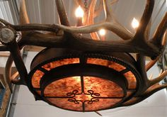 Elk Mica Chandelier 545 9+4-Light Elk Antler and Mica Chandelier - Genuine Antler  This chandelier provides a beautiful amber glow through the mica tiers while retaining a rustic elegance feel of an antler chandelier.  Medium and small elk antler circle the center with tall patina coated copper sleeves for the 9 candles. This chandelier is custom built by the artist in Colorado USA.