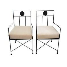 A stunning set of four black wrought iron cafe chairs with elegant thin lines and round medallion decoration on the backs. Custom white duck cushions . Seat height 20.5