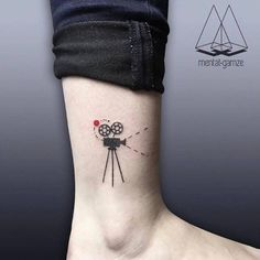 Film camera tattoo on the ankle.