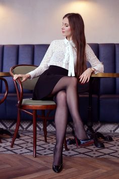 Biała koronkowa koszula, rozkloszowana spódniczka mini, czarne rajstopy i szpilki