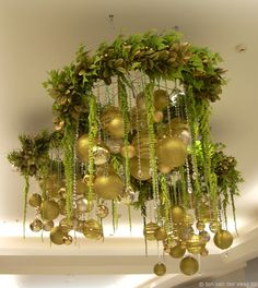 wreath over top of taller vase with lime green and pink floral accents with the pin or green glass balls and hanging amaranthes on top of the lights