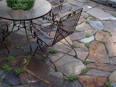 another patio idea...I like this look, but only if the grass between the stones is more uniform - this just looks weedy to me.  I also wonder if the patio furniture would get caught in the cracks?