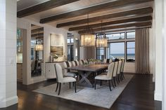 Amanda Webster Design: Transitional Coastal Color Interior Design / Photo: Neil Rashba / Dining Room, crystal industrial iron chandelier, antique mirror panels, stained wood beams, v-joint plank ceiling, penny joint plank walls, stained wood farm table
