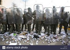 Line of Chilean police in full anti riot gear receiving paper balls from students protesting in Santiago de Chile Stock Photo