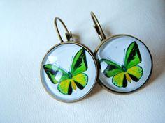 Boucles d'oreilles, en bronze, avec des cabochons en verre de 18mms de diamètre représentant un papillon vert.  Bague assortie, disponible en bouti...