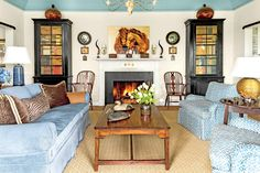 """The Living Room - The Art of Living Small - Southernliving. """"A limited color palette gives clarity. Blues and whites predominate in this house, playing well with the clients' classic furnishings. Too many colors can shrink a room—the eye has to stay very busy to take it all in. Painting the walls white and the vaulted portion of the ceiling celestial blue makes the 14-foot ceilings soar even higher."""""""