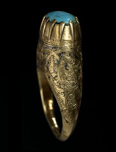 A Seljuk nielloed gold Ring with turquoise seal   Persia, 12th-13th Century  cast in gold, with oval bezel with eleven prongs securing a kufic inscribed turquoise stone, the shoulders engraved and inlaid with roundels containing birds on a scrolling interlace arabesque   1.8cm. diam.