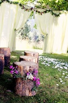 Such an easy way to set up a backyard wedding: a rope across two trees and hang a flowy curtain overtop. Decorate with wildflowers….AND OH MY the best…LOG CHAIRS. Beautifully simple, easy, elegant,...