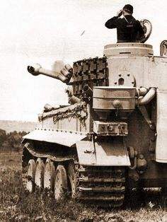A Tiger Tank Commander watches Stuka attack in distance.