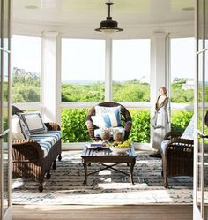 An indoor-outdoor rug inscribed in French with a story about an ant and a grasshopper covers the porch floor. - Traditional Home ® / Photo: John Bessler / Design: Jane Forman