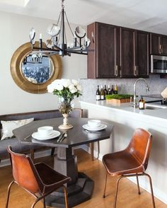 Small space with tons of style!! Design by @elizabethmillerreich Rich wood and leather against classic white counters, amazing seating options and geometric table! #dining #kitchendining #eatinkitchen #diningarea #breakfastnook #diningroom #kitchendesign #kitchen #kitchendecor #kitchentable #chairs #bench #wood #leather #diningtable  #chandelier #cabinets #mirror #countertop #backsplash #sink #home #homedecor #homedesign #interior #interiordesign #interiordecor #interiorstyle