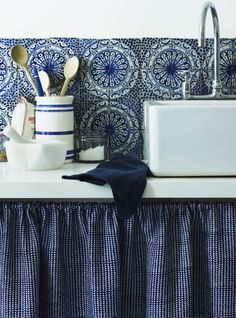A simple below-counter curtain offers a charming alternative to kitchen cupboards. The blue and white patterned tiles and counter-top ceramics evoke a summery, Mediterranean feel. Out of the Blue. Homes & Gardens, Photography Jan Baldwin, Styling Emma Thomas