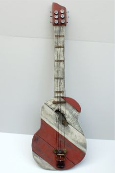 Pallet Wood Guitar. Handmade by Jim Harmon form AT Bear Hollow. Pallet wood, old belt buckle, rusty tin, bailing wire, and shotgun shells were used. wood with knot holes knocked out were sued to make the hole by careful placement. Check with me to make similar. All are one of a kind in some way.