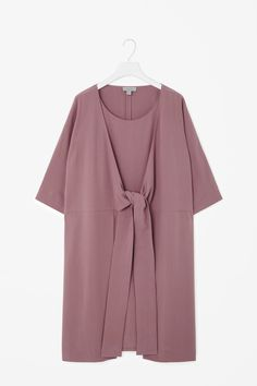 An oversized fit, this double layered dress is made from a fluid material with a grown on tie detail at the front. A slip-on design, it has half kimono sleeves, in-seam pockets and blind stitch finishes. Abaya Fashion, Muslim Fashion, Modest Fashion, Fashion Dresses, Casual Hijab Outfit, Elegant Outfit, Fashion Vestidos, Hijab Stile, Nursing Wear