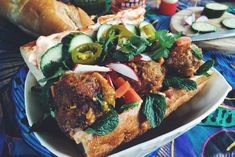 A delicious spin on a banh mi sandwich recipe using cilantro lamb meatballs, pickled vegetables, kewpie mayo, herbs, and french bread.