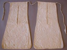 """Title: Pockets, pair  Collection: Amgueddfa Cymru, Sain Ffagan, Caerdydd/National Museum Wales St Fagans/Cardiff  Date early-mid 1700s  The fronts of this carefully-made pair of attached pockets are each formed from two pieces of linen, lined and hand quilted with flowers, stems and leaves, possibly re-cycled older pieces. Mainly intact, the quilting is done with white thread in back stitch probably using a fine internal cord for a raise..."" http://www.vads.ac.uk/large.php?uid=94290=1"
